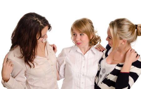 High angle portrait of three young female companions standing in a close embrace chatting or gossiping together isolated on white Stock Photo - 16795845