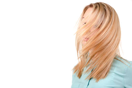 windblown: Head and shoulders portrait of a blonde woman with the wind in her hair blowing across and obscuring her face isolated on white with copyspace