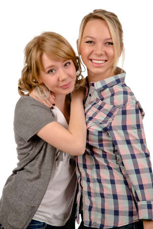 Two happy young women relaxing together standing with their arms around each others necks smiling at the camera, studio portrait isolated on white photo