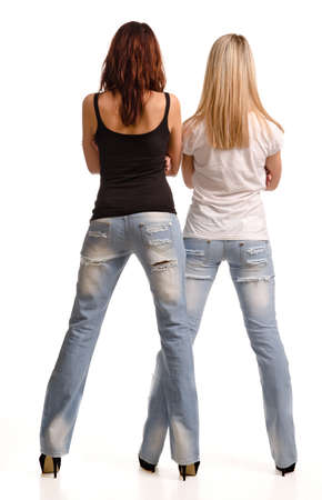tight fitting: Rear view of two sexy shapely young girls in tight fitting jeans and summer tops standing side by side isolated on white Stock Photo