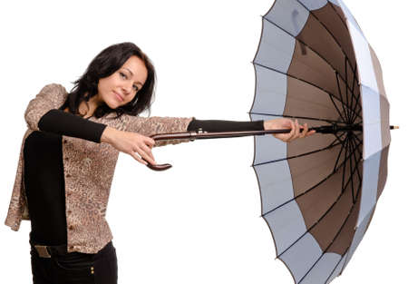 gusty: Beautiful Caucasian young brunette woman holding an umbrella with her stretched arm Stock Photo
