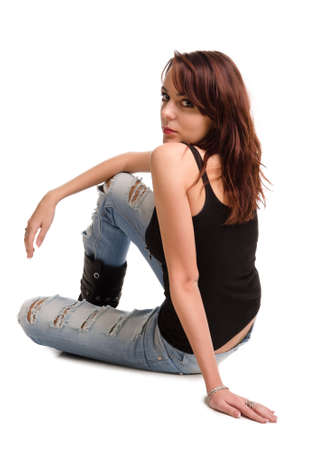 Beautiful young casual redhead woman or student in ragged designer jeans relaxing on the floor looking back over her shoulder at the camera on a white background photo