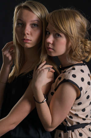 Two attractive scared young women standing close together in the shadows staring at the camera with sombre expressions Stock Photo - 17566071