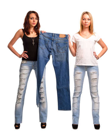 raggedy: Two beautiful fashion concious women wearing modern raggedy designer jeans holding up a pair of old blue denim jeans on display isolated on white Stock Photo