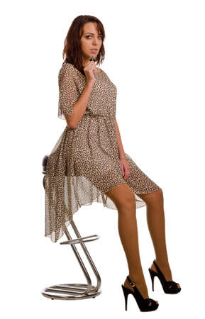 barstool: Attractive young woman in a see through dress and stilettoes posing sitting on a modern chrome barstool isolated on white Stock Photo