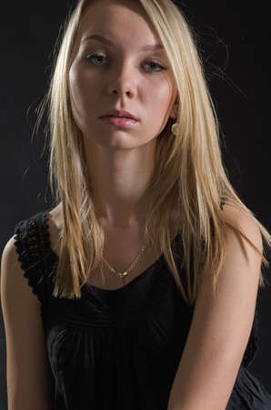 Upper body portrait of a serious young blonde woman posing in a stylish black dress against a dark background photo