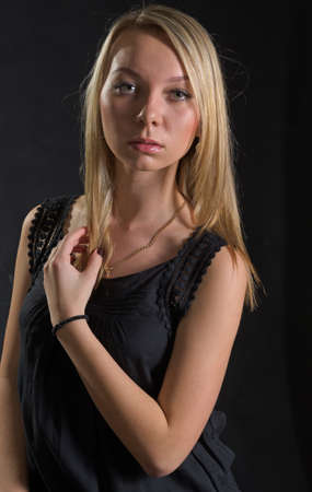 Beautiful serious young blonde lady in stylish black eveningwear posing against a dark studio background photo