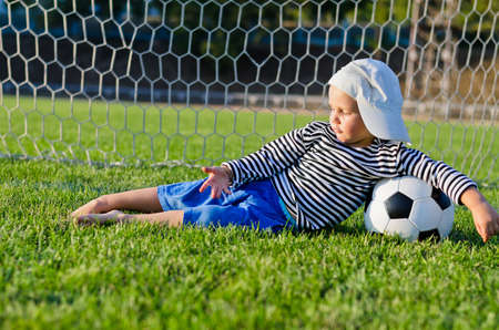 Small barefoot boy in a cap lying relaxing on the green grass in the goalposts with his arm draped over a soccer ball