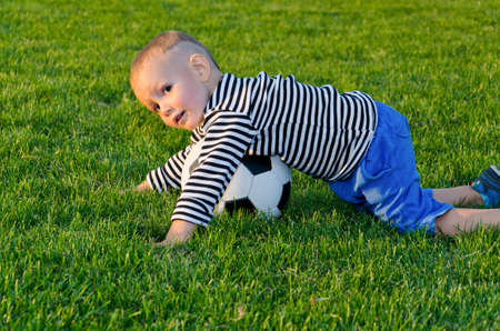 Small boy having fun playing soccer on a grassy green field crouched low over the ball in soft evening light photo