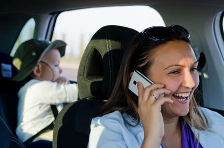 Woman driver with a young boy strapped into a child safety seat in the back of the car laughing and chatting on her mobile phone
