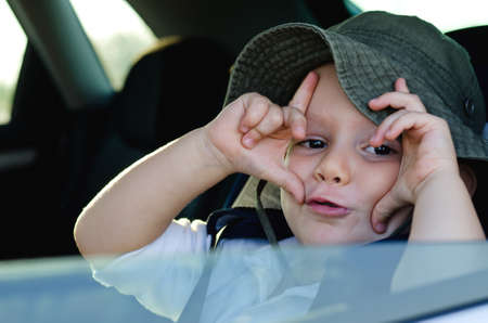 Mischievous little boy gesturing at the camera making a frame shape with his fingers on either side of his eyes as he sits waiting in the rear of a motor car Stock Photo - 17657814