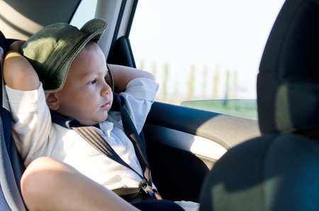 safety harness: Little boy in a child safety seat sitting patiently in the back of a car with his hands behind his head staring out of the window Stock Photo