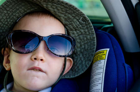 Cute little boy in a sun hat sitting in a car looking out of the window wearing his mothers sunglasses Stock Photo - 17657777