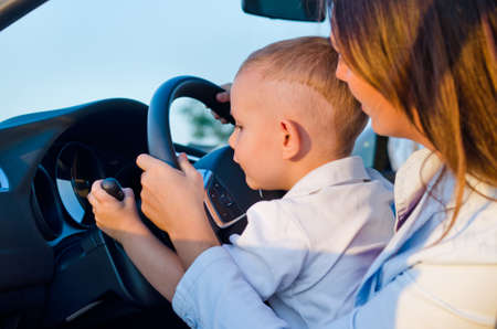 Cute curious small boy sitting on his mothers lap behind the steering wheel pretending to learn to drive testing out the hand controls on the steering column Stock Photo