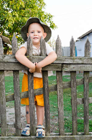 Happy little boy in colourful orange shorts and a sun hat standing between the slats of a a wooden picket fence photo