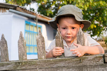 come home: Cute little boy with a worried expression clinging to an old slatted wooden fence in his sunhat waiting for Dad to come home