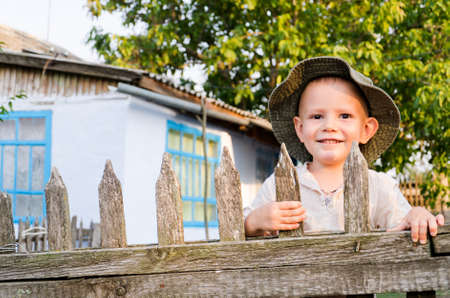 Beaming happy little boy in a sunhat standing holding on to the slats of a wooden picket fence enjoying the summer sunshine photo