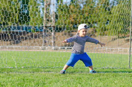 Cute little boy playing at being a goalkeeper on a sportsfield standing in the goalposts defending the the line photo