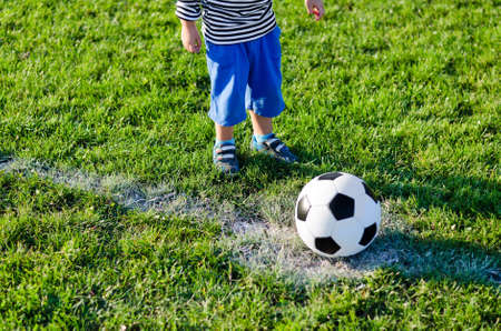 Cropped view image of the legs of a little child about to kick off the soccer ball from the centre line on a green grassy sportsfield photo