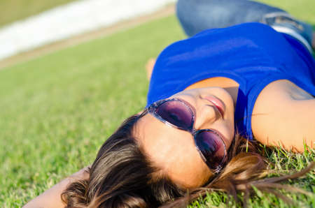 sprawled: Woman wearing sunglasses relaxing in the sun lying sprawled out on the green grass on her back, view from the top of the head Stock Photo
