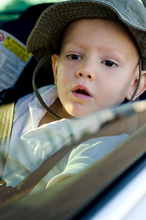 strapped: Adorable little boy wearing a hat waiting in a car strapped into a child safety seat and peering out of the open passenger window Stock Photo