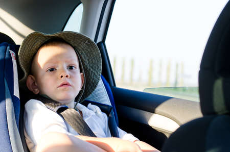 Cute little boy passenger in a car sitting quietly on the back seat in his child safety seat