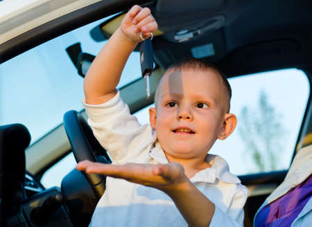 Little boy sitting inside a car playiing with the car keys dangling them teasingingly above his mothers outstretched hand Stock Photo - 17826393