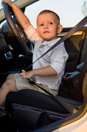 Cute little boy sitting strapped into the safety belt in the drivers seat of a car with his hand on the steering wheel looking at the camera Stock Photo - 17826410