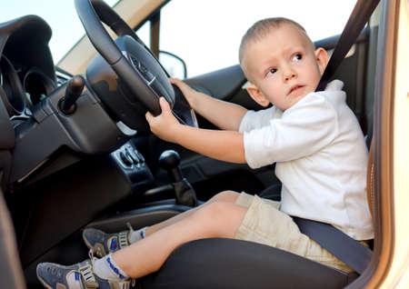 Schattige kleine jongen beweert te rijden vastgebonden in stevig op de bestuurders stoel van een auto met zijn handen op het stuur