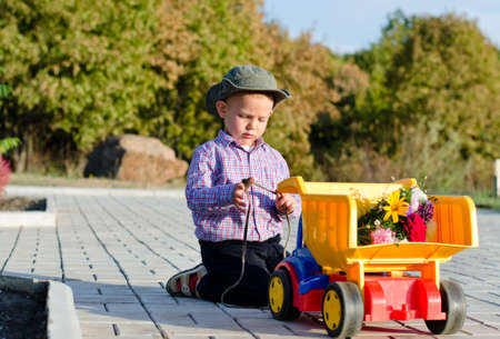 Cute little boy in a summer sun hat kneeling on a paved driveway playing with a large colourful plastic toy truck Stock Photo - 17826420