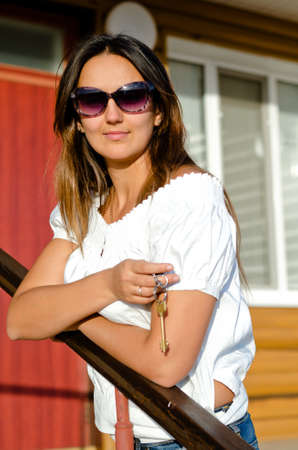 Attractive smiling woman wearing sunglasses standing on steps in front of a house holding a house key in her hand photo