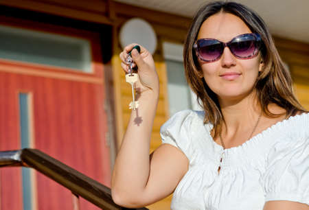 Smiling attractive woman wearing sunglasses holding a house door key in her hand as she stands in front of a colorful entrance to her home or rental accomodation photo