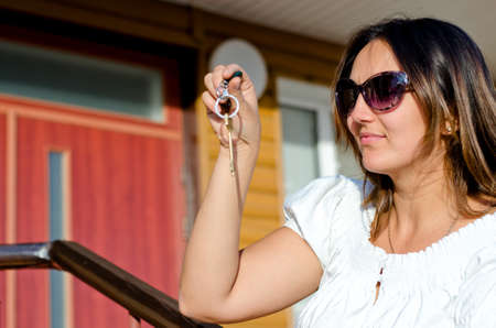 Smiling woman wearing sunglasses holding up the key to a property dangling from her hand conceptual of ownership or rental of a residence or vacation house photo
