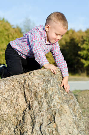 Young boy clambering on rocks with a look of concentration as he tries to find a handhold while exploring outdoors photo