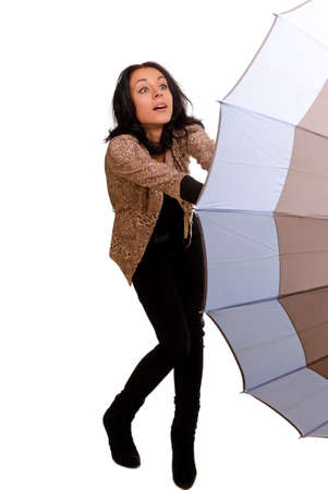 gusty: Beautiful stylish young woman struggling with an umbrella trying to hold on to it in the wind isolated on white