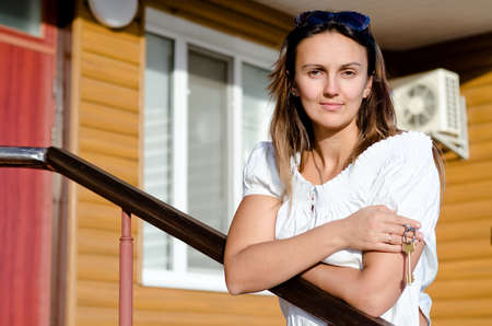 Smiling beautiful casual young woman standing outside her house in the sunshine with the key to the door dangling in her hand Stock Photo - 17892601