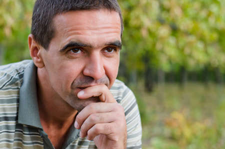 Thoughtful concerned good-looking mature man sitting outdoors against a green leafy background with his chin on his hand planning and thinking for the future