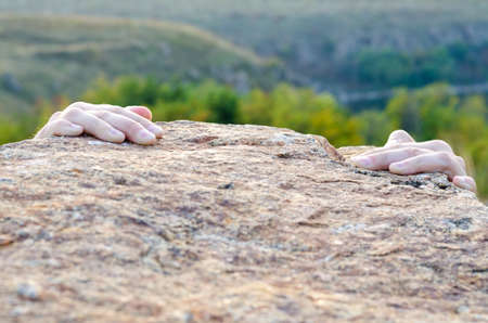 Male climber gripping a rocky ledge with just his fingertips in view on the granite against a valley backdrop