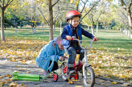training wheels: Cute little boy learning to ride his new bicycle fitted with training wheels helped by his young sister as the two play together in the park
