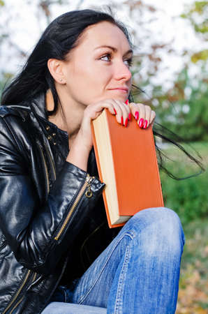 introspective: Thoughtful woman sitting outdoors staring into the distance with her chin resting a book Stock Photo