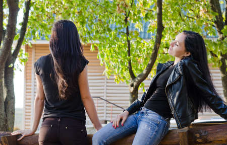 facing away: Two women chatting outdoors relaxing on a garden bench with one facing away from the camera Stock Photo