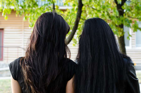 facing away: Rear view of two longhaired brunette women standing side by side outdoors in the garden facing away from the camera Stock Photo