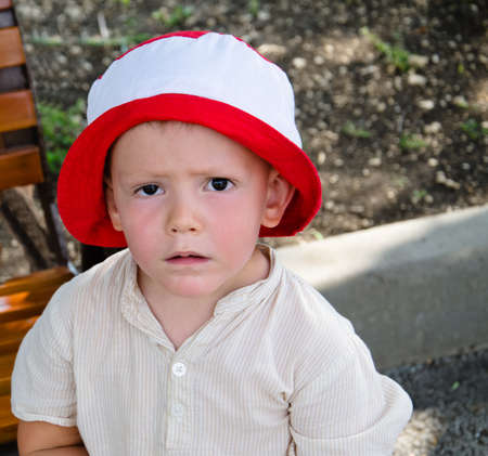woebegone: Sad little boy with a woebegone expression standing in a red and white sunhat looking at the camera
