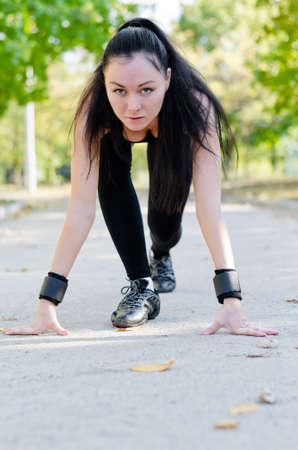 crouched: Woman athlete in the starting position for a run crouched down on a rural road facing the camera in a park as she starts her training