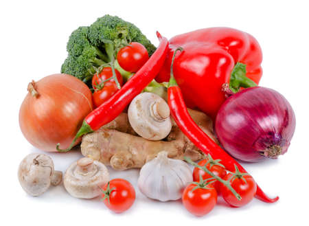 High angle view of a selection of fresh farm vegetables including, peppers, tomato, chilli, onions, mushrooms and broccoli on a white studio background