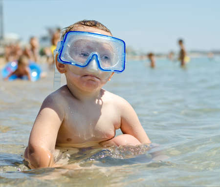 bathers: Small boy sitting in the shallow water near the seashore wearing goggles with holidaymakers enjoying themselves at the seaside visible in the distance