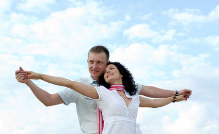 courting: Low angle view of a beautiful loving couple celebrating the joy of life standing close together with their arms outspread against a cloudy blue sky Stock Photo