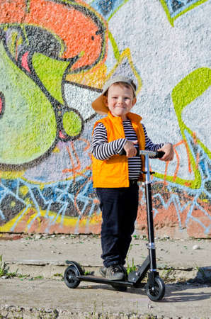 Proud little boy with his scooter standing in the sunshine with his baseball cap at a rakish angle smiling at the camera, backdrop of a wall covered in colourful graffiti photo