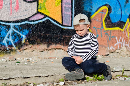 Little boy sitting sulking with a pouting expression on the pavement in front of a brightly coloured wall covered in graffriti photo