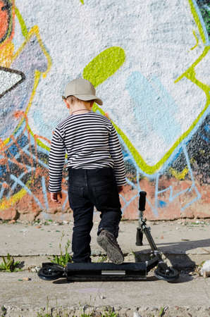 Little boy with his back to the viewer walking away from his scooter which is lying on the sidewalk towards a wll covered in colourful graffiti art